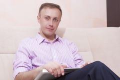 Homme bel positif dans l'habillement de style d'affaires se reposant sur Couc Image libre de droits
