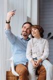 Homme bel positif tenant un smartphone Photographie stock libre de droits