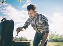 Homme bel préparant le barbecue pour des amis équipez faire cuire la viande sur le barbecue - chef mettant quelques saucisses et  Photographie stock libre de droits