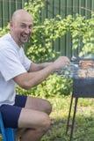 Homme bel préparant le barbecue pour des amis Photos libres de droits