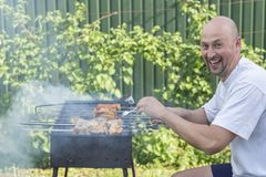 Homme bel préparant le barbecue pour des amis Jeunes couples faisant le barbecue dans leur jardin Photos stock