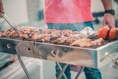 Homme bel pr?parant le barbecue pour des amis Main de jeune homme grillant une certains viande et l?gume photo stock