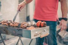 Homme bel pr?parant le barbecue pour des amis Main de jeune homme grillant une certains viande et l?gume photographie stock libre de droits