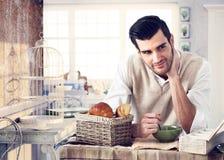 Homme bel prenant le petit déjeuner dans l'intérieur de cottage images stock