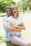 Homme bel prenant son amie riante en parc Images stock