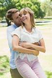 Homme bel prenant son amie riante en parc Photo stock