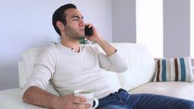 Homme bel répondant au téléphone tout en détendant sur son sofa clips vidéos