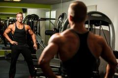 Homme bel regardant dans le miroir après séance d'entraînement de musculation Photographie stock