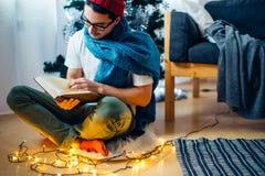 Homme bel regardant le livre comme cadeau de Noël photos stock
