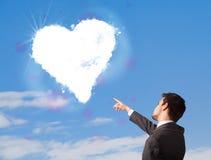 Homme bel regardant le nuage blanc de coeur sur le ciel bleu Photos stock