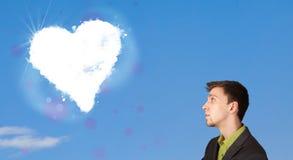 Homme bel regardant le nuage blanc de coeur sur le ciel bleu Photos libres de droits