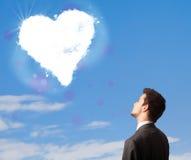 Homme bel regardant le nuage blanc de coeur sur le ciel bleu Photo stock