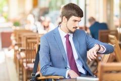 Homme bel regardant le temps la montre photographie stock libre de droits