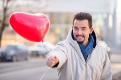 Homme bel riant heureux offrant un ballon à air rouge en forme de coeur Mode de vie urbain et concept roman photographie stock