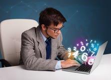 Homme bel s'asseyant au bureau et dactylographiant sur l'ordinateur portable avec le nombre 3d Images libres de droits