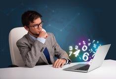 Homme bel s'asseyant au bureau et dactylographiant sur l'ordinateur portable avec le nombre 3d Image libre de droits