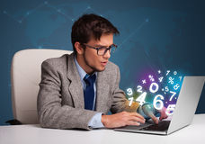 Homme bel s'asseyant au bureau et tapant sur l'ordinateur portable avec le numéro 3d Photographie stock libre de droits
