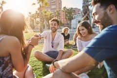 Homme bel s'asseyant avec des amis riant et plaisantant Photos libres de droits