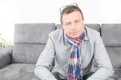 Homme bel s'asseyant confortablement sur le divan photos libres de droits