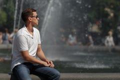 Homme bel s'asseyant dans des lunettes de soleil sur le fond de fontaine, à partir de l'appareil-photo Photographie stock libre de droits