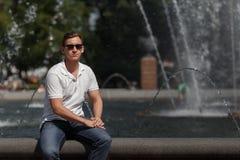 Homme bel s'asseyant dans des lunettes de soleil sur le fond de fontaine, regardant l'appareil-photo Images libres de droits