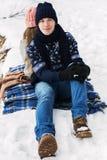 Homme bel s'asseyant dans la forêt d'hiver sur la neige Image stock