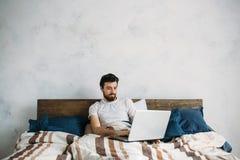 Homme bel s'asseyant dans le lit Photo stock