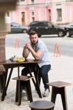 Homme bel s'asseyant en café extérieur de vegan Photo libre de droits