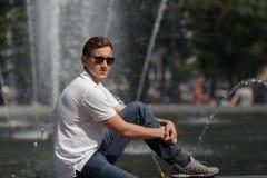 Homme bel s'asseyant et souriant dans des lunettes de soleil sur le fond de fontaine Photo libre de droits
