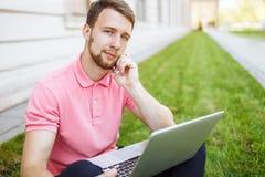 Homme bel s'asseyant sur l'herbe dans la ville avec un ordinateur portable et parlant au téléphone, recherche d'emploi photo stock