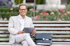 Homme bel s'asseyant sur le banc Photos stock