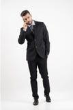 Homme bel sûr dans le costume au téléphone marchant vers l'appareil-photo regardant loin Photographie stock libre de droits