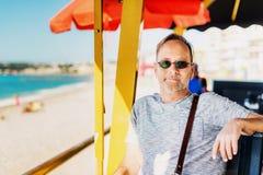 Homme bel se reposant au café de plage de bord de la mer Photographie stock libre de droits