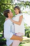 Homme bel se soulevant vers le haut de son amie en parc Photo stock