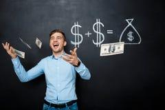 Homme bel se tenant au-dessus du tableau noir avec le concept tiré du dollar Photographie stock libre de droits