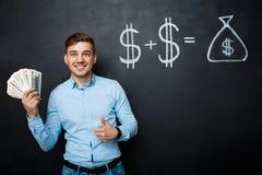 Homme bel se tenant au-dessus du tableau noir avec le concept tiré du dollar Photos stock