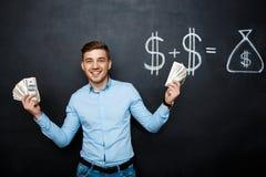 Homme bel se tenant au-dessus du tableau noir avec le concept tiré du dollar Image stock