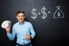 Homme bel se tenant au-dessus du tableau noir avec le concept tiré du dollar Images libres de droits