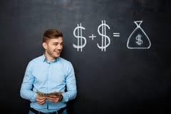 Homme bel se tenant au-dessus du tableau noir avec le concept tiré du dollar Photo stock