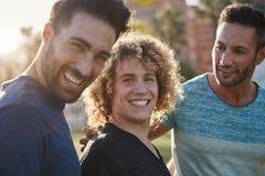 Homme bel se tenant avec des amis en dehors de rire Image stock