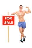 Homme bel se tenant prêt a à vendre le signe Photographie stock