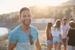 Homme bel se tenant sur la plage avec son rire d'amis Photographie stock libre de droits