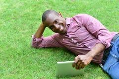 Homme bel se trouvant sur la pelouse avec le comprimé image libre de droits