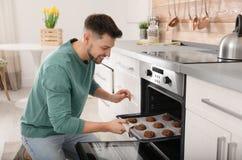Homme bel sortant le plateau des biscuits cuits au four du four photos stock