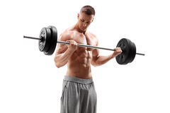 Homme bel soulevant un barbell lourd Photo stock