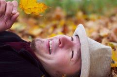 Homme bel souriant et se situant dans des lames d'automne images libres de droits