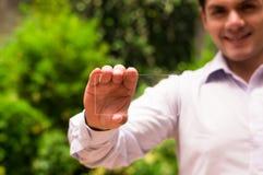 Homme bel souriant tandis qu'il tient le téléphone intelligent transparent futuriste dans sa main Photos stock