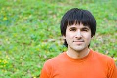 Homme bel sur le fond d'herbe verte photographie stock libre de droits