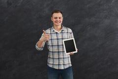 Homme bel tenant le comprimé numérique dans le studio Images stock