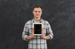 Homme bel tenant le comprimé numérique dans le studio Photo stock